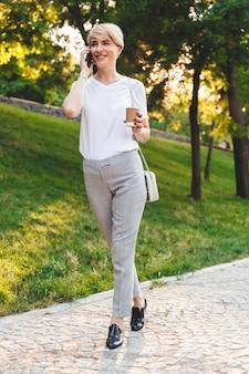 Foto a figura intera di elegante donna bionda che indossa abbigliamento casual sorridente, mentre passeggia nel parco verde della città con caffè da asporto e parla al telefono cellulare