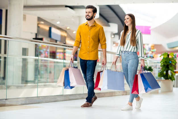 Foto a figura intera di due persone allegre bella signora bel ragazzo coppia godersi il tempo libero comprare tenere molte borse camminare centro commerciale pavimento indossare jeans casual camicia scarpe vestito al chiuso
