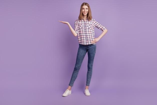 La foto a tutta lunghezza della ragazza mostra l'offerta promozionale del prodotto che pubblicizza suggerisce isolato su uno sfondo di colore viola