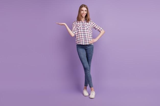 La foto a figura intera della ragazza mostra l'offerta promozionale del prodotto consiglia di consigliare isolata su sfondo di colore viola