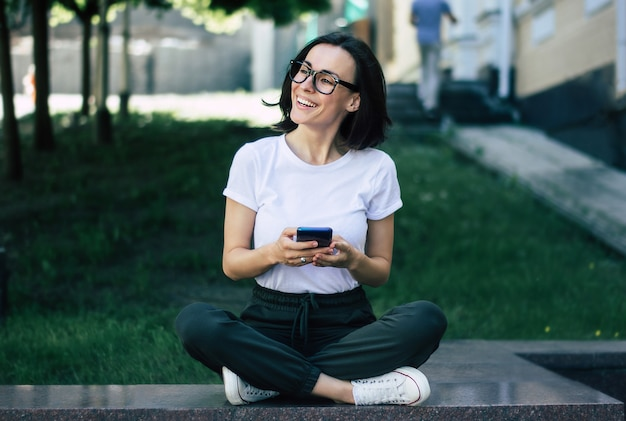 Foto a figura intera di una giovane ragazza, con gli occhiali sul viso, con in mano un telefono, sorridente, che si diverte fuori.