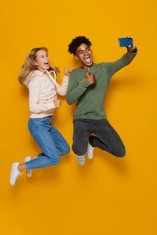 Foto a figura intera di giovani studenti uomo e donna 16-18 che ridono e si fanno selfie mentre saltano, isolati su sfondo giallo