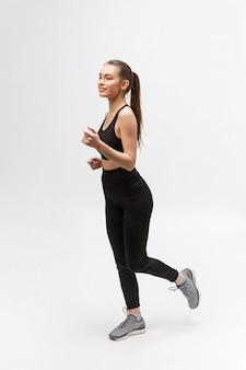 Foto a figura intera di una donna sportiva in esecuzione in studio
