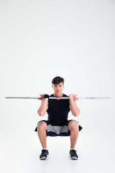 Ritratto integrale dell'uomo atletico che fa gli esercizi accovacciati con il bilanciere isolato