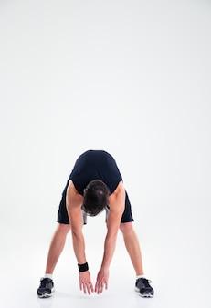 Ritratto integrale dell'uomo atletico che fa gli esercizi di allungamento isolati