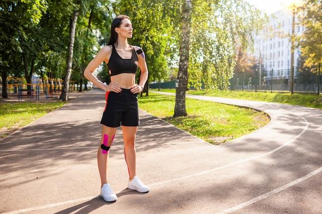 Ritratto integrale della donna castana muscolare attraente che porta attrezzatura nera di sport che posa all'aperto.