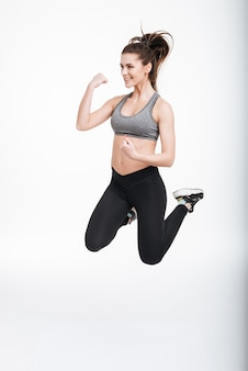 Ritratto integrale della donna attraente di sport che salta isolato