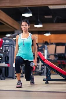 Ritratto integrale della donna attraente allenamento con manubri in palestra