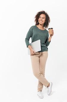Ritratto a figura intera di una giovane donna africana attraente in piedi isolata su un muro bianco, con in mano un computer portatile e una tazza di caffè da asporto