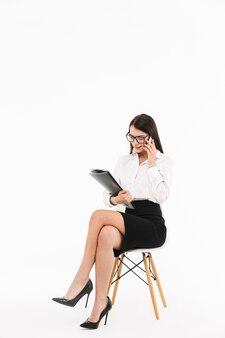 Ritratto a figura intera di una giovane donna d'affari attraente in abbigliamento formale seduto su una sedia isolata sul muro bianco, utilizzando il telefono cellulare, in possesso di una cartella