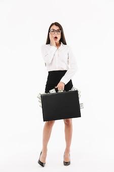 Ritratto a figura intera di una giovane donna d'affari attraente in abiti formali in piedi isolato su un muro bianco, con valigetta