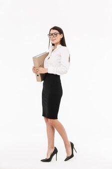 Ritratto a figura intera di una giovane donna d'affari attraente in abiti da cerimonia in piedi isolato su un muro bianco, con in mano una cartella