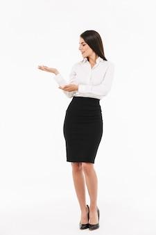 Ritratto a figura intera di una giovane donna d'affari attraente in abiti formali in piedi isolato su un muro bianco, presentando lo spazio della copia