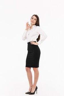 Ritratto a figura intera di una giovane donna d'affari attraente che indossa abiti formali in piedi isolato su un muro bianco, ok?