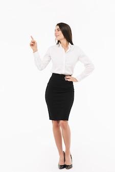 Ritratto a figura intera di una giovane donna d'affari attraente che indossa abiti formali in piedi isolato su un muro bianco, indicando lo spazio della copia