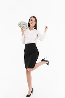 Ritratto a figura intera di una giovane donna d'affari attraente che indossa abiti formali in piedi isolato su un muro bianco, mostrando banconote in denaro, celebrando