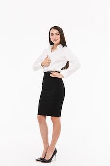Ritratto a figura intera di una giovane donna d'affari attraente che indossa abiti formali in piedi isolato su un muro bianco, pollice in alto