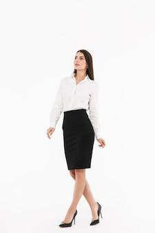 Ritratto a figura intera di una giovane donna d'affari attraente che indossa abiti formali che cammina isolata su un muro bianco
