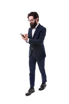 Ritratto integrale di un uomo d'affari barbuto con uno smartphone