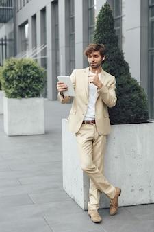 Ritratto integrale di giovane uomo d'affari barbuto in vestito beige che ha videochiamata sulla tavoletta digitale all'aperto
