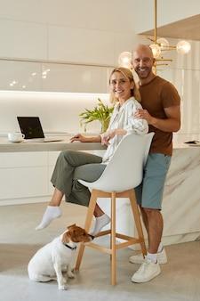 Ritratto a figura intera di bella coppia adulta seduto al bancone della cucina in interni domestici