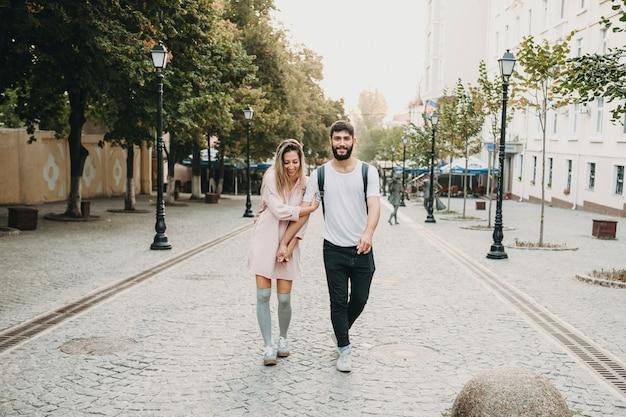 Ritratto integrale di una bella coppia che cammina per strada mentre l'uomo sta guardando la telecamera sorridendo mentre lei sta abbracciando il suo braccio sorridendo e guardando fuori mentre esplora nuove città.