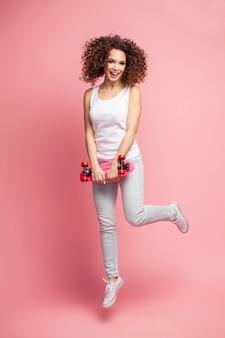 Ritratto integrale di bella donna felice in abiti estivi in posa e distogliere lo sguardo mentre salta e tiene lo skateboard isolato sopra il rosa.