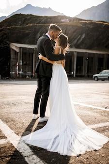 Ritratto integrale di una bella coppia di sposi romantici che si abbracciano e si baciano contro il tramonto.