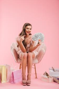 Ritratto integrale di bella donna del cliente in vestito che punta il dito su un sacco di soldi in mano mentre era seduto in poltrona con gli acquisti, isolato sopra il muro rosa