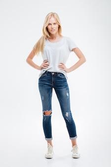 Ritratto a figura intera di una bella ragazza sorridente con le braccia sui fianchi isolate sul muro bianco