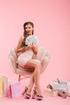 Ritratto integrale di bella donna in vestito che tiene ventilatore di soldi mentre era seduto in poltrona con borse della spesa e scarpe, isolato sopra il muro rosa