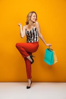 Ritratto integrale di una bellissima giovane donna bionda in piedi su sfondo giallo, portando le borse della spesa