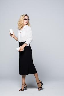 Ritratto integrale di bella giovane donna di affari nell'usura convenzionale che cammina e che manda un sms sul telefono delle cellule con il caffè da asporto in mano isolato sopra il muro grigio.