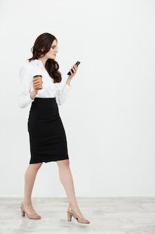 Ritratto integrale di bella giovane donna di affari nell'usura convenzionale che cammina e che manda un sms sul telefono delle cellule con il caffè da asporto in mano isolato