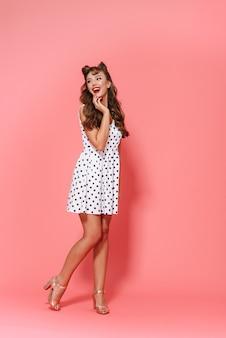 Ritratto integrale di una condizione d'uso del vestito dalla bella giovane ragazza pin-up isolata, in posa