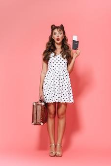 Ritratto integrale di una bella giovane ragazza pin-up che indossa un abito in piedi isolato, mostrando il passaporto con biglietto aereo, portando la valigia