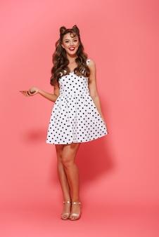 Ritratto integrale di un vestito da portare della bella giovane ragazza pin-up in piedi isolato, utilizzando il telefono cellulare