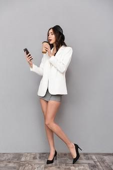 Ritratto integrale di una bella giovane donna vestita in minigonna e giacca su sfondo grigio, bere caffè, utilizzando il telefono cellulare