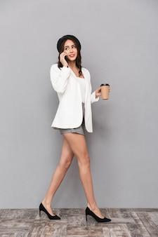 Ritratto integrale di una giovane e bella donna vestita in minigonna e giacca su sfondo grigio, tenendo la tazza di caffè, parlando al telefono cellulare, camminando