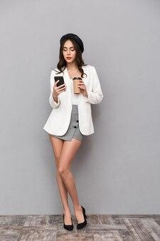Ritratto integrale di una bella giovane donna vestita in minigonna e giacca su sfondo grigio, tenendo la tazza di caffè, utilizzando il telefono cellulare