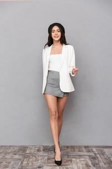 Ritratto integrale di una giovane e bella donna vestita in minigonna e giacca che cammina su sfondo grigio, guardando la fotocamera