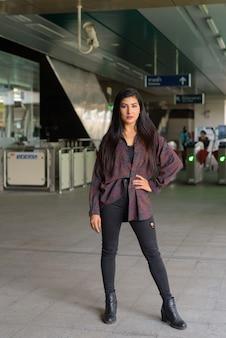 Ritratto a figura intera di bella giovane donna in piedi all'aperto