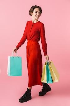 Ritratto integrale di bella giovane donna che indossa vestiti rossi in piedi isolati, portando i sacchetti della spesa