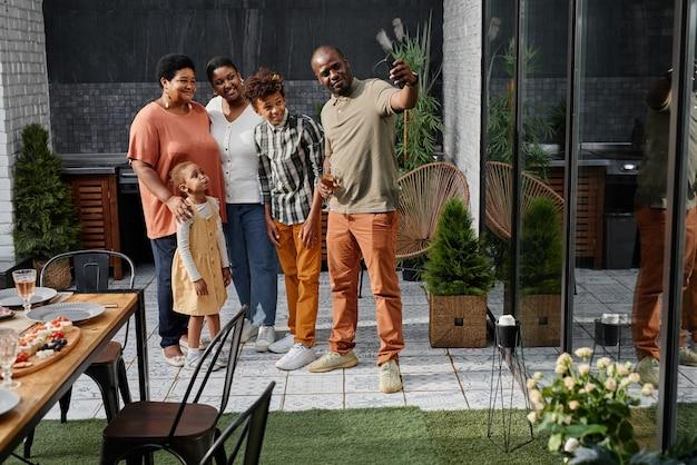 Ritratto a figura intera di una grande famiglia afroamericana che scatta foto selfie insieme mentre si gode la cena...
