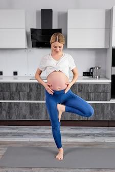 Ritratto a figura intera di donna bionda in abiti sportivi in piedi su una gamba accarezzando la pancia, meditando in cucina a casa