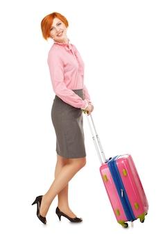 Ritratto integrale di una donna d'affari in viaggio d'affari in piedi con una valigia da viaggio rosa