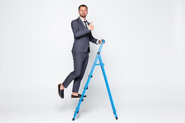 Ritratto integrale di un uomo d'affari con i pollici in su che sale una scala isolata su fondo bianco