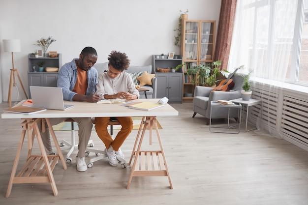 Ritratto a figura intera di padre afroamericano premuroso che aiuta il figlio a fare i compiti o a studiare mentre si siede insieme alla scrivania nell'interno di casa, copia spazio