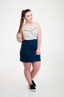Ritratto a figura intera di una donna grassa casual in piedi isolata su un muro bianco