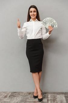 Ritratto integrale della donna caucasica che indossa vestiti di affari che tiene fan di soldi e che mostra pollice su, isolato sopra il muro grigio
